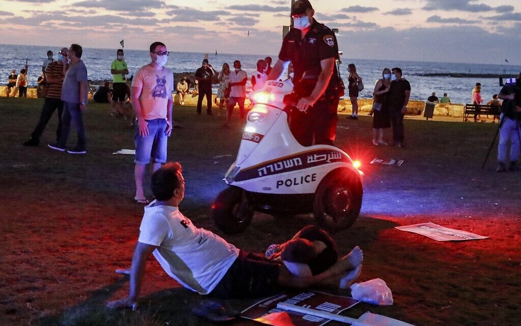 An Israeli policeman speaks with protesters from atop a scooter during a demonstration in Charles Clore Park in the Mediterranean coastal city of Tel Aviv on July 18, 2020 (Jack GUEZ / AFP)