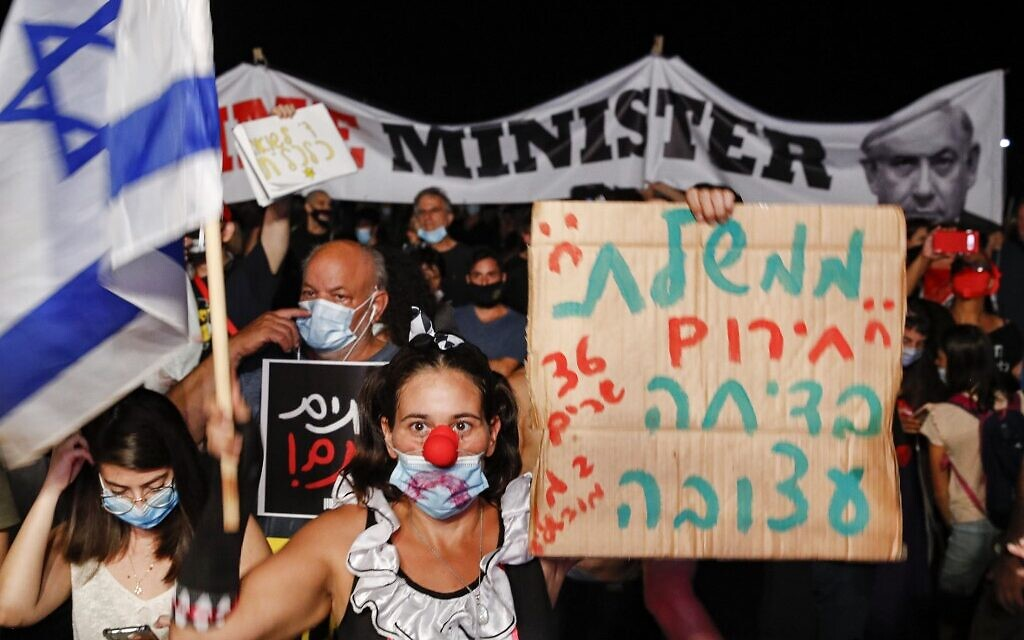 An anti-government protester dressed as a clown and wearing a mask due to the coronavirus pandemic raises a sign reading 'The emergency government is a sad joke' during a demonstration in Charles Clore Park in Tel Aviv on July 18, 2020. (Jack Guez/AFP)