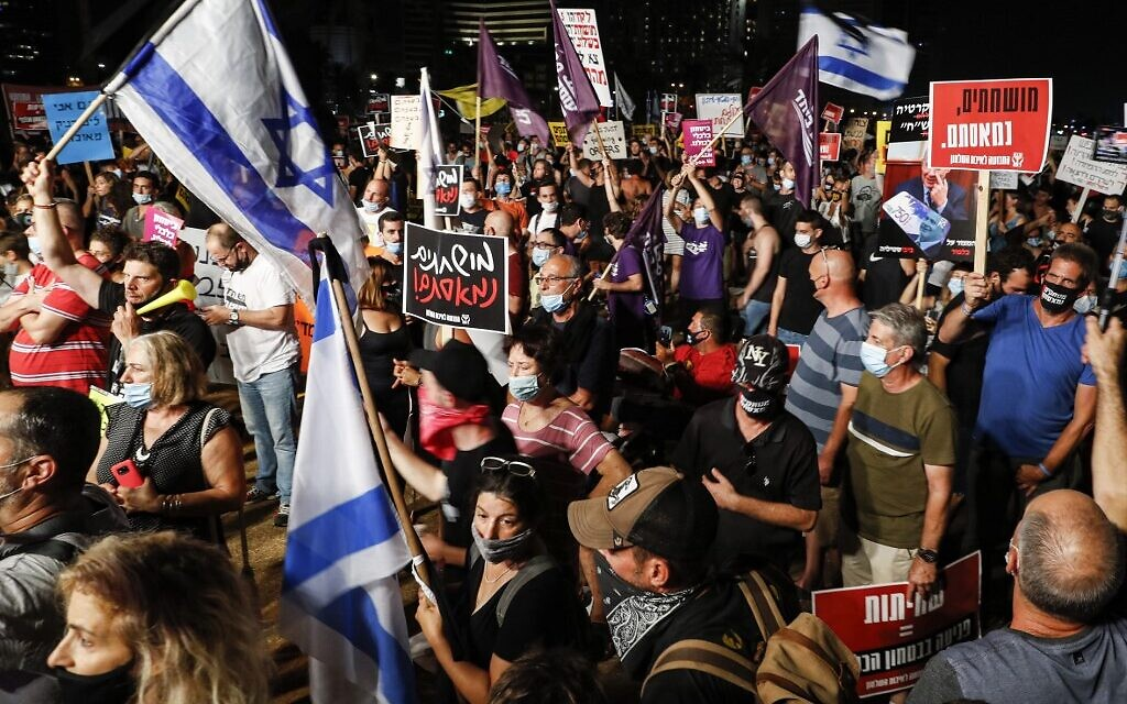 Anti-government protesters, clad in masks due to the COVID-19 coronavirus pandemic, gather with Israeli flags and signs during a demonstration in Charles Clore Park in the Mediterranean coastal city of Tel Aviv on July 18, 2020 (Jack GUEZ / AFP)