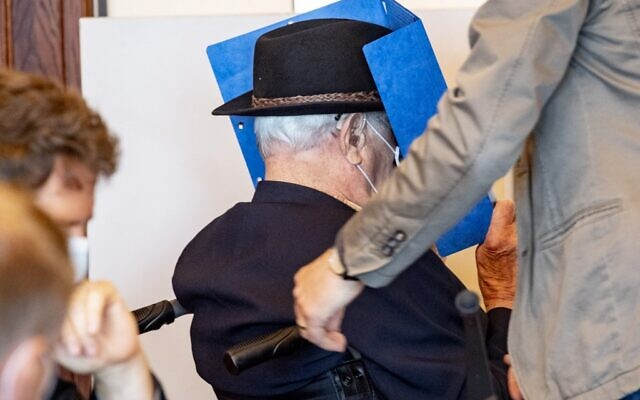 Bruno Dey, a former SS-watchman at the Stutthof concentration camp, hides his face behind a folder as he arrives on a wheelchair for a hearing in his trial on July 20, 2020 in Hamburg, northern Germany (Axel Heimken / POOL / AFP)