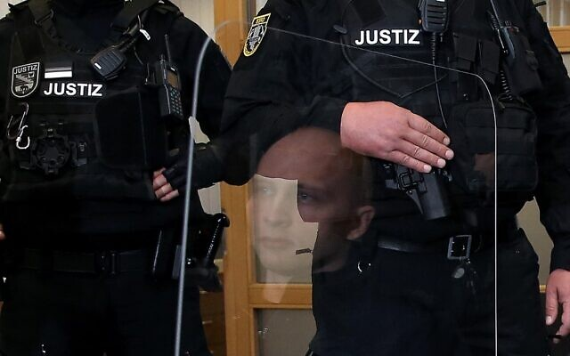 Stephan Balliet (C), who is accused of shooting dead two people after an attempt to storm a synagogue in Halle an der Saale, eastern Germany, is reflected in a transparent barrier in a courtroom at the second day of his trial on July 22, 2020 in Magdeburg, eastern Germany. (Ronny HARTMANN / various sources / AFP)