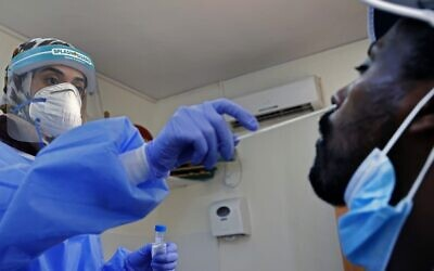 A medic collects a swab sample from a man at a coronavirus testing facility in Or Yehuda, on July 22, 2020. (Jack Guez/ AFP)