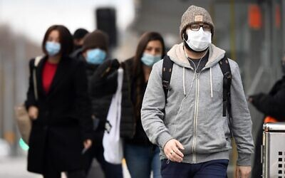 Commuters walk past Melbourne's Flinders Street Station on July 23, 2020, on the first day of the mandatory wearing of face masks in public areas as the city experiences an outbreak of the COVID-19 coronavirus. (William WEST / AFP)