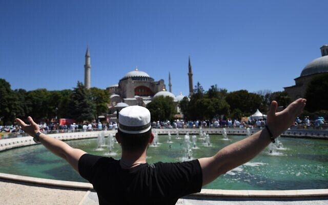 A man raises his arms as people gathe on July 24, 2020 outside Hagia Sophia in Istanbul to attend the Friday prayer, the first Muslim prayer held at the landmark since it was reconverted to a mosque despite international condemnation. (OZAN KOSE / AFP)