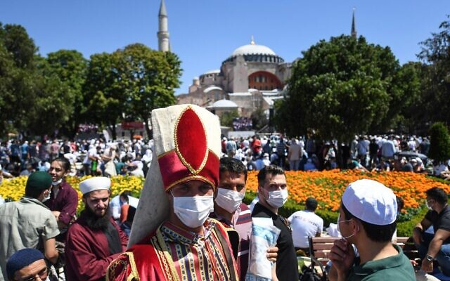 A man wearing a traditional Ottoman costume arrives with others on July 24, 2020 outside Hagia Sophia in Istanbul to attend the Friday prayer, the first Muslim prayer held at the landmark since it was reconverted to a mosque despite international condemnation. (OZAN KOSE / AFP)