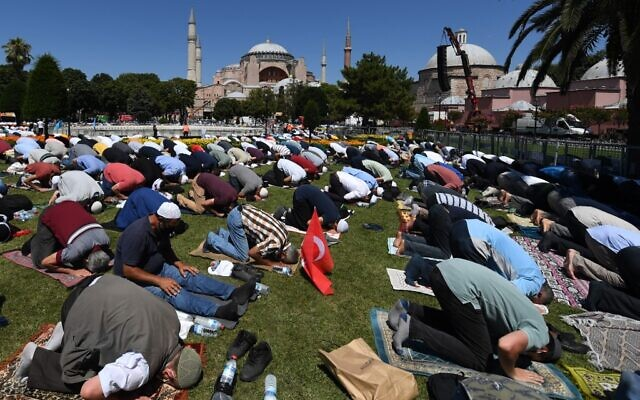 Men take part in the Friday prayer on July 24, 2020 outside Hagia Sophia in Istanbul, the first Muslim prayer held at the landmark since it was reconverted to a mosque despite international condemnation. (OZAN KOSE / AFP)
