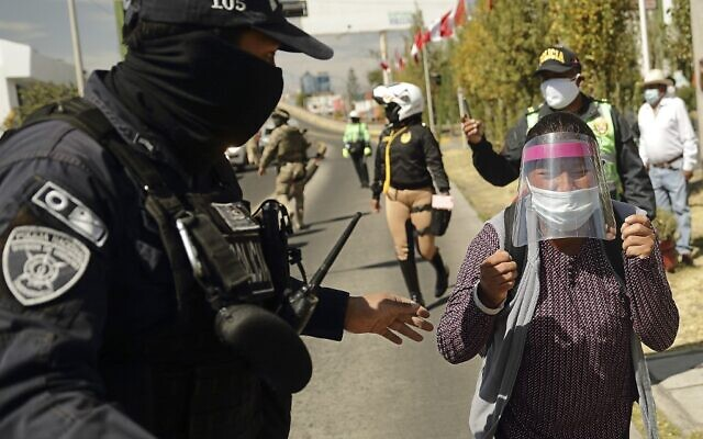 A policeman stops Celia Capira Mamani, while attempting to reach the car of Peru's President Martin Vizcarra to demand medical attention for her husband Adolfo Mamani Tacuri, infected with the novel coronavirus COVID-19, during the latter's visit to the Honorio Delgado Hospital in the southern Andean city of Arequipa on July 19, 2020 (Denis MAYHUA / AFP)