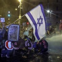 Protesters crouch down as police use water cannons against them in Jerusalem on July 25, 2020. (AHMAD GHARABLI / AFP)