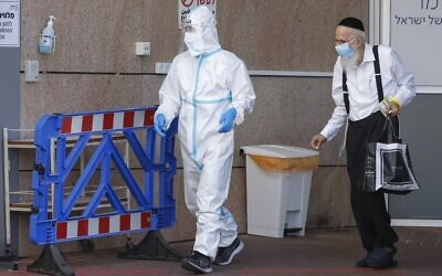 A medical worker in a protective suit accompanies a man who tested positive for COVID-19 at Sheba Medical Center in Ramat Gan on July 26, 2020. (Jack Guez/AFP)