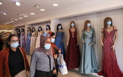 Palestinian women wearing protective masks amid the COVID-19 pandemic, shop at a clothing store as Muslims prepare for the Eid al-Adha feast, in the West Bank city of Hebron, on July 27, 2020. (HAZEM BADER / AFP)
