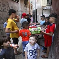 Palestinian children gather around a street vendor in the Amari refugee camp near the West Bank city of Ramallah on July 29, 2020. (ABBAS MOMANI / AFP)