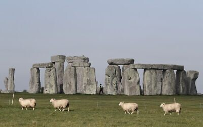 Sheep graze as security guards patrol the prehistoric monument at Stonehenge in southern England, on April 26, 2020, closed during the national lockdown due to the novel coronavirus COVID-19 pandemic.  (Adrian DENNIS / AFP)