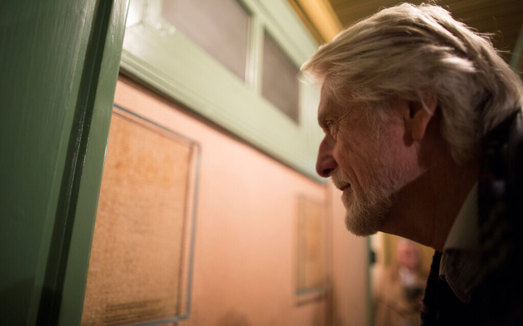 A visitor examines pencil marks measuring the growth of Anne and Margot Frank in what used to be their parents' room, at the Anne Frank House museum in Amsterdam, November 24, 2016. (Photo Collection Anne Frank House/ via JTA)