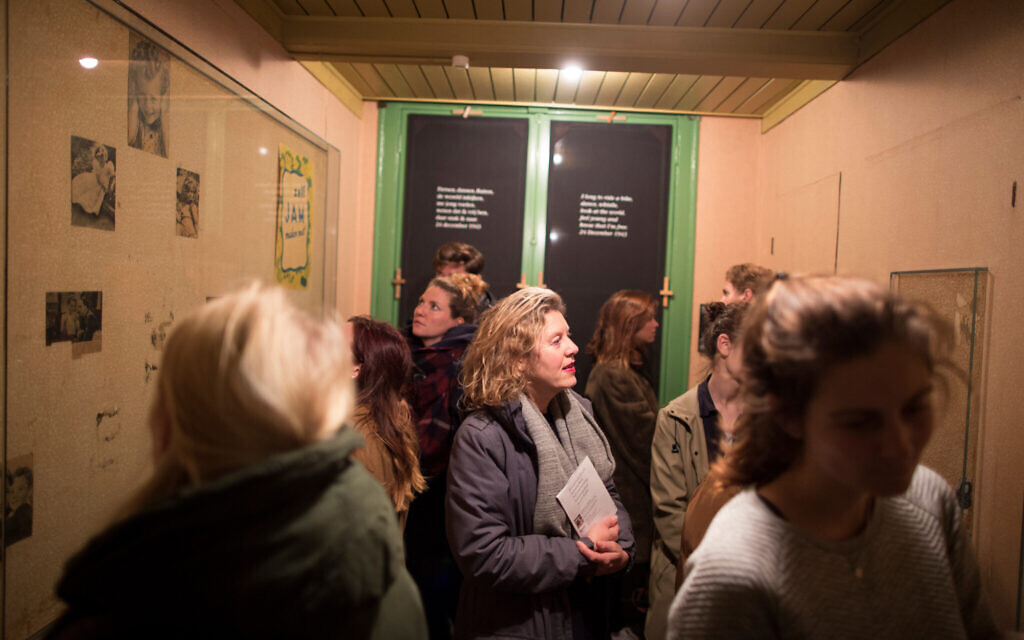 Visitors study the room that used to be Anne Frank's at the museum devoted to her memory in Amsterdam, November 24, 2016. (Photo Collection Anne Frank House/ via JTA)