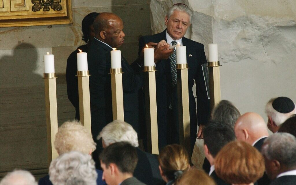 John Lewis, D-Ga., and Norbert Bikales, who was part of the Kindertransport from Berlin to France in July 1939 following the deportation of his parents and brother to Poland, light one of six candles representing the more than six million Jews who were killed during the Holocaust, in a ceremony in the rotunda of the U.S. Capitol in Washington, D.C., April 9, 2002. (Scott J. Ferrell/Congressional Quarterly/Getty Images via JTA)