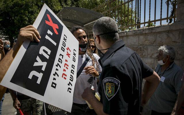 Jerusalem municipality inspector speaks to a demonstrator near Prime Minister Benjamin Netanyahu's official residence in Jerusalem on July 13 2020 (Olivier Fitoussi/Flash90)