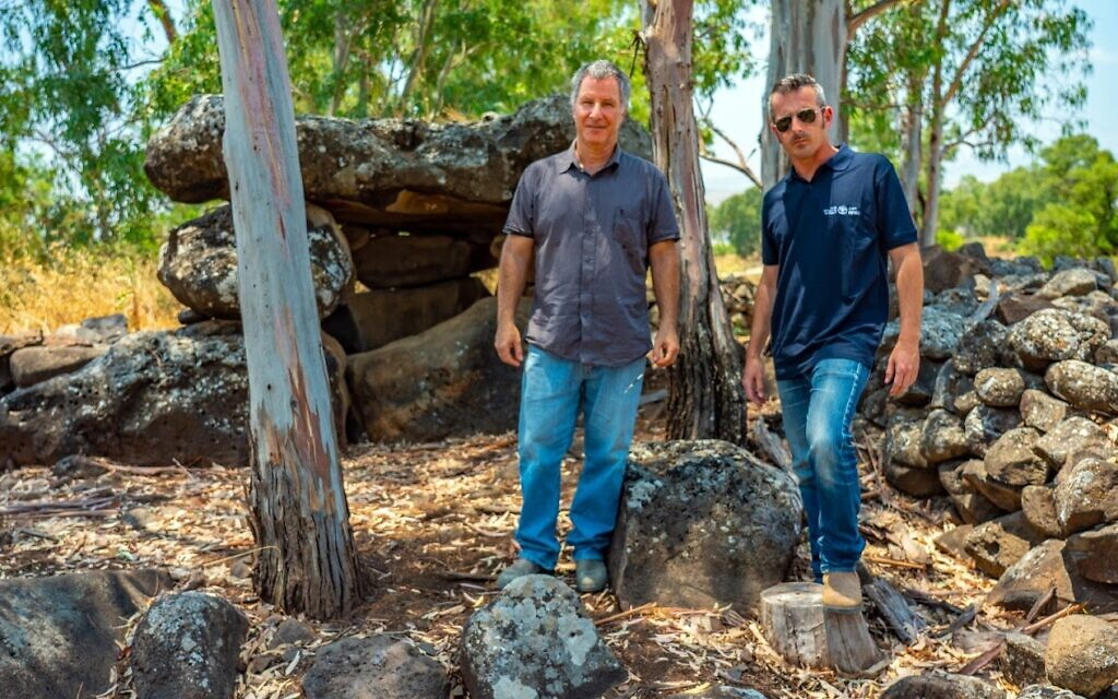 Researchers Prof. Gonen Sharon of Tel-Hai College (left) and Uri Berger of the Israel Antiquities Authority, with the dolmen discovered in the Yehudiya Nature Reserve. (Yaniv Berman, Israel Antiquities Authority)