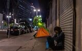 A homeless woman is seen sleeping on the street of Skid Row during the COVID-19, coronavirus pandemic in Los Angeles, California on May 16, 2020. (Apu Gomes/AFP via Getty Images)