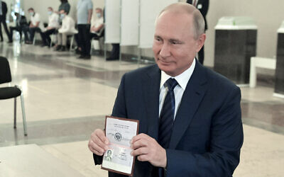 Russian President Vladimir Putin shows his passport to a member of an election commission as he arrives to take part in voting at a polling station in Moscow, Russia, July 1, 2020. (Alexei Druzhinin, Sputnik, Kremlin Pool Photo via AP)