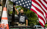 In this June 19, 2020, file photo, George Floyd's name is written on the windshield as John Coy wears a shirt that reads Black Lives Matter and stands through his sunroof with his fist in the air at 16th Street Northwest renamed Black Lives Matter Plaza near the White House in Washington.  (AP Photo/Andrew Harnik)