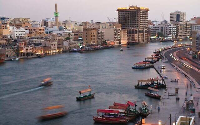 In this photograph taken with a slow shutter speed, traditional abra boats navigate the Dubai Creek in Dubai, United Arab Emirates on July 1, 2020. (AP Photo/Jon Gambrell)