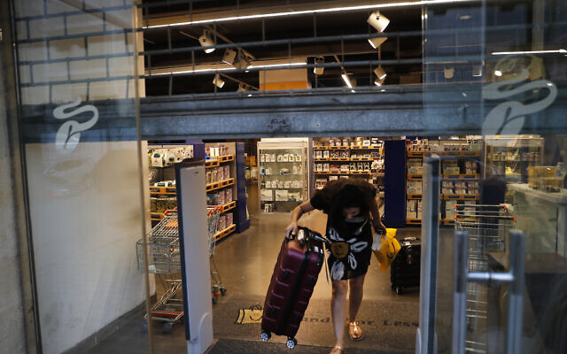 A customer carries luggage out of an international fashion and home-ware retailer temporarily shutting down, in Beirut, Lebanon, on July 2, 2020. (AP Photo/Hussein Malla)