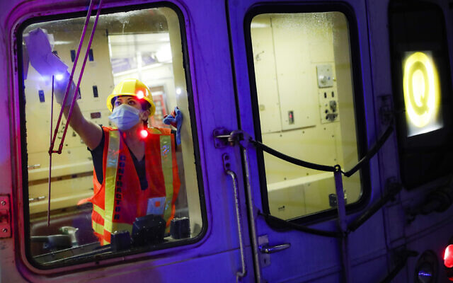 A contractor cleans a subway car at the 96th Street station to control the spread of COVID-19, Thursday, July 2, 2020, in New York. Mass transit systems around the world have taken unprecedented — and expensive — steps to curb the spread of the coronavirus, including shutting down New York subways overnight and testing powerful ultraviolet lamps to disinfect seats, poles and floors. (AP Photo/John Minchillo)