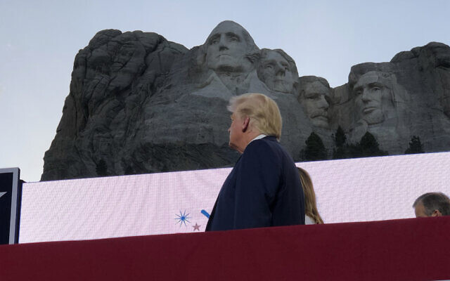 US President Donald Trump watches as planes perform fly-overs of the Mount Rushmore National Monument Friday, July 3, 2020, in Keystone, S.D. (AP Photo/Alex Brandon)