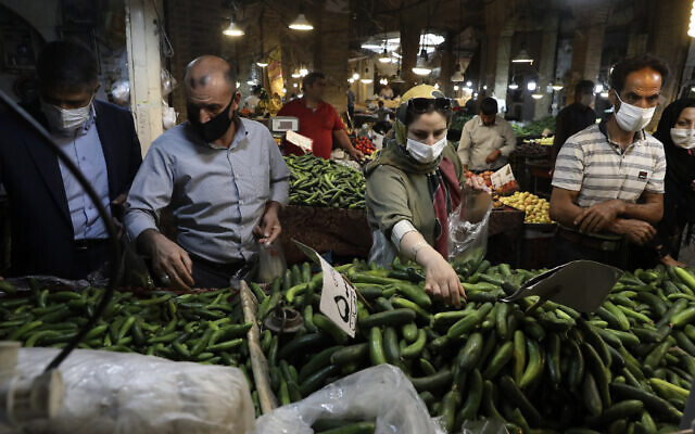 People wearing face masks to help prevent the spread of the coronavirus shop at the old grand bazaar of the Iranian city of Zanjan on July 5, 2020. (AP/Vahid Salemi)