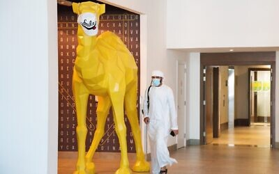 An Emirati wearing a face mask due to the coronavirus pandemic walks past a camel statue decorated with a face mask at the Rove City Centre Hotel in Dubai, United Arab Emirates, July 6, 2020. (Jon Gambrell/AP)