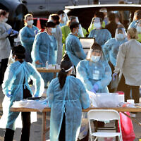 Medical personnel prepare to test hundreds of people lined up in vehicles in Phoenix's western neighborhood of Maryvale for free COVID-19 tests organized by Equality Health Foundation, June 27, 2020. (AP Photo/Matt York, File)