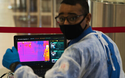 In this June 10, 2020, photo, an official wearing a mask due to the coronavirus pandemic operates a temperature screening point at Dubai International Airport's Terminal 3 in Dubai, United Arab Emirates. (AP Photo/Jon Gambrell)