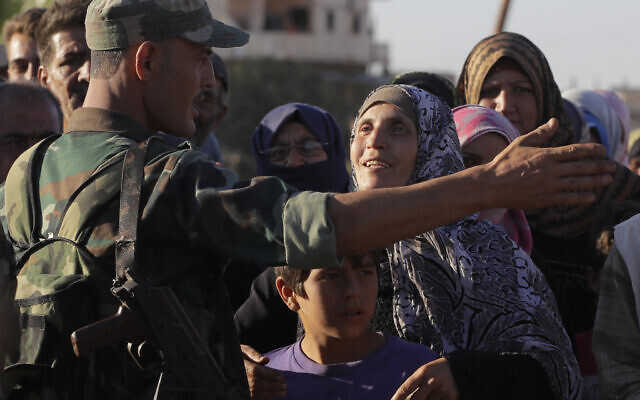 In this August 15, 2018 file photo, a woman talks with a soldier of the Syrian army during distribution of humanitarian aid from the Russian military in the town of Rastan, Syria. (AP Photo/Sergei Grits, File)
