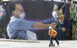 A construction worker rides a scooter past a mural by Hiero Veiga of billionaire businessman Moishe Mana, left, and City of Miami Mayor Francis X. Suarez wearing masks, July 13, 2020, in the Wynwood Arts District of Miami. (AP Photo/Wilfredo Lee)
