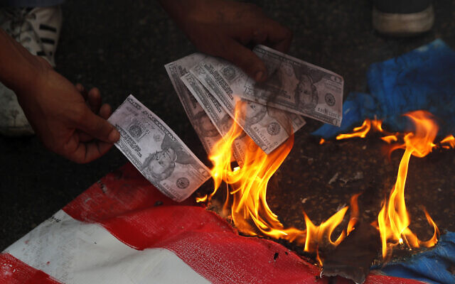 A supporter of a communist group burns representation of US currency, during a protest against US interference in Lebanon's affairs, near the US embassy, in Aukar northeast of Beirut, Lebanon,  July 10, 2020. (Hussein Malla/AP)