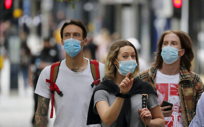 Shoppers wearing protective face masks walk along Oxford Street in London, July 14, 2020. (AP Photo/Frank Augstein)