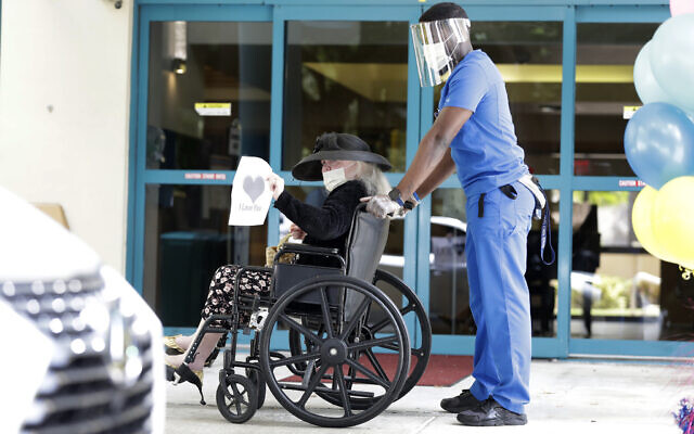 Margaret Choinacki, center, 87, who has no other family members left because her husband and daughter have died, waves goodbye after a drive-by visit by her friend Frances Reaves, as resident care coordinator Anggy Volmar, right, wheels her back inside, Friday, July 17, 2020, at Miami Jewish Health in Miami (AP Photo/Wilfredo Lee)