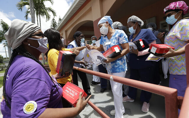 Union members hand out masks and lunches to workers at the Franco Nursing & Rehabilitation Center, on July 20, 2020, in Miami (AP Photo/Wilfredo Lee)