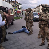 An assailant, who seized a long-distance bus with 10 hostages, lies on the ground after police officers captured him in the city centre of Lutsk, some 400 kilometers (250 miles) west of Kyiv, Ukraine on Tuesday July 21, 2020. The assailant was armed and carrying explosives, according to a Facebook statement by Ukrainian police. (Ukrainian Police Press Office via AP)