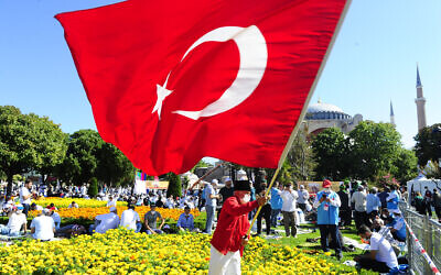 A man waves a Turkish flag outside the Byzantine-era Hagia Sophia, in the historic Sultanahmet district of Istanbul, Friday, July 24, 2020.  (AP Photo/Omer Kuscu)