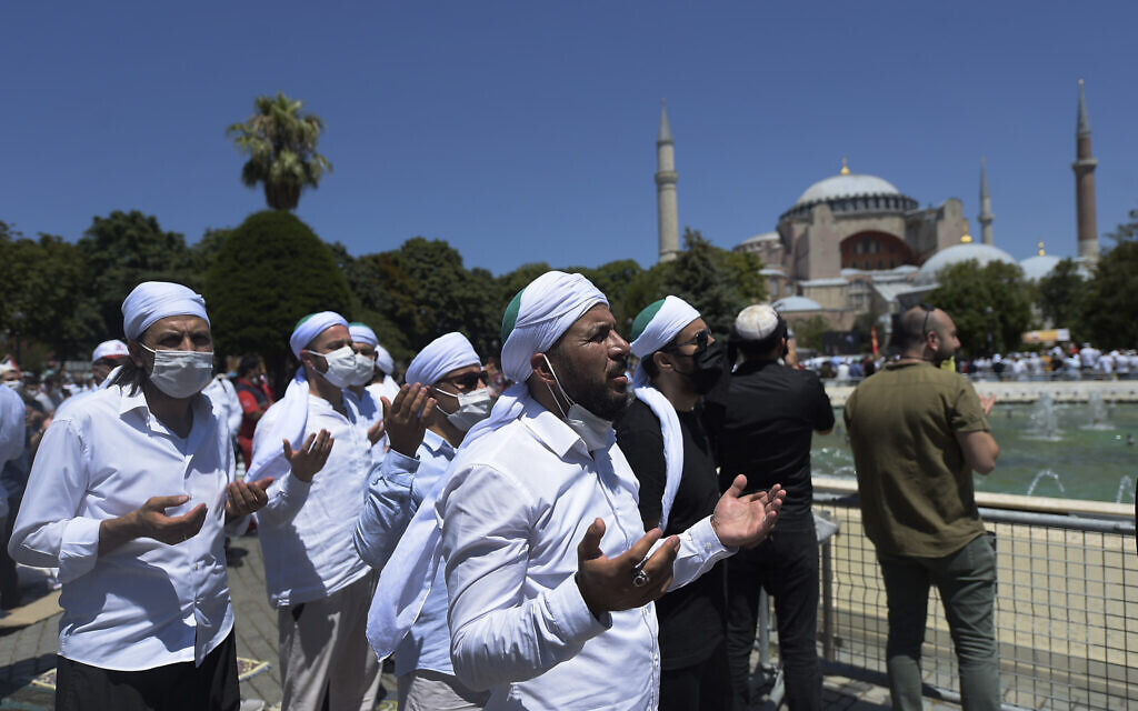 Muslims pray during Friday prayers at the historic Sultanahmet district of Istanbul, near the Byzantine-era Hagia Sophia, background, Friday, July 24, 2020. (AP Photo/Yasin Akgul)