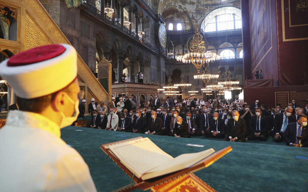 An imam reads from the Quran, Islams holy book, as dignitaries including Turkey's President Recep Tayyip Erdogan take part in Friday prayers in Hagia Sophia, at the historic Sultanahmet district of Istanbul, Friday, July 24, 2020. (Turkish Presidency via AP, Pool)
