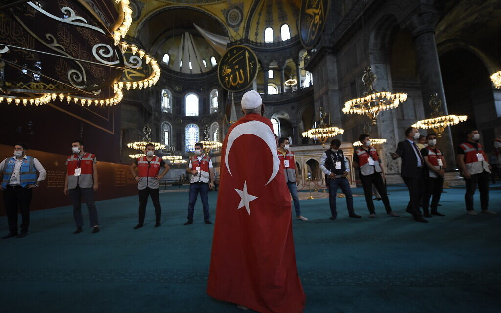A man draped in a Turkish flag stands as people walk inside the Byzantine-era Hagia Sophia following the inaugural Friday prayers, in the historic Sultanahmet district of Istanbul, Friday, July 24, 2020. Worshipers held the first Muslim prayers in 86 years inside the Istanbul landmark that served as one of Christendom's most significant cathedrals, a mosque and a museum before its conversion back into a Muslim place of worship. The conversion of the edifice, has led to an international outcry. (AP Photo/Yasin Akgul)