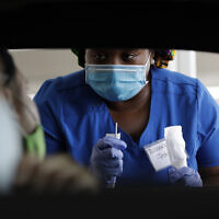 Healthcare worker Rahaana Smith instructs passengers how to use a nasal swab, on Friday, July 24, 2020, at a drive-thru coronavirus testing site in Miami. (AP/Wilfredo Lee)