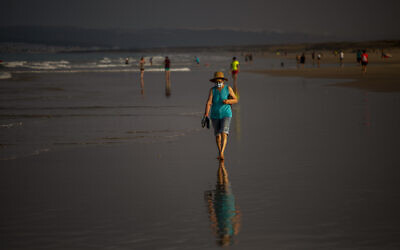 A woman wearing a face mask walks at the beach in Zahara de los Atunes, Cadiz province, south of Spain, on July 25, 2020. (AP Photo/Emilio Morenatti)