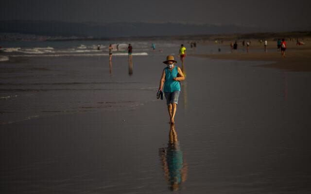 A woman wearing a face mask walks at the beach in Zahara de los Atunes, Cadiz province, south of Spain, on July 25, 2020. (AP Photo/Emilio Morenatti)
