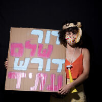 Kalanit Sharon, 31, poses for a photo during a protest against Prime Minister Benjamin Netanyahu, outside his residence in Jerusalem, July 23, 2020. Hebrew on her sign reads 'An entire generation demands a future.' (AP Photo/Oded Balilty)
