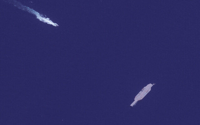 In this July 26, 2020, satellite photo provided on July 27, by Maxar Technologies, an Iranian fast boat, top left, approaches a mockup aircraft carrier built by Iran in the Strait of Hormuz. (Maxar Technologies via AP)
