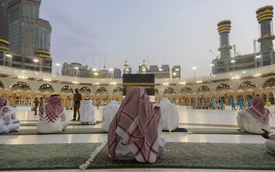 Pilgrims pray around the Kaaba, the square structure in the Great Mosque, toward which believers turn when praying, in Mecca, Saudi Arabia, July 26, 2020. (Saudi Ministry of Media via AP)