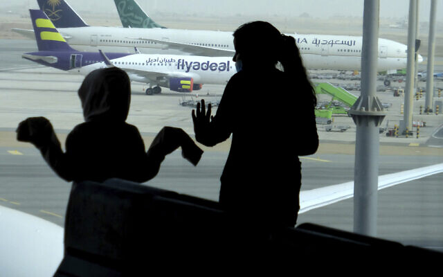 Passengers watch aircraft on the tarmac as they wait for their flight at the King Abdulaziz International Airport in Jiddah, Saudi Arabia, on July 28, 2020.  (AP Photo/Amr Nabil)